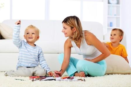 Mother and children sitting on the carpet and drawing with crayons.
